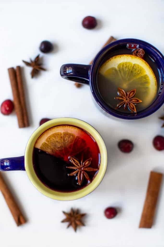 Two glasses full of mulled with with sliced orange and star anise.
