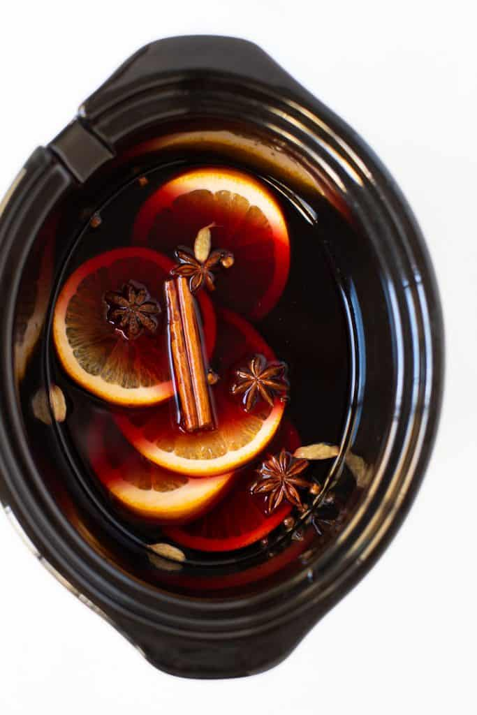 Crockpot full of mulled wine with sliced oranges and spices.