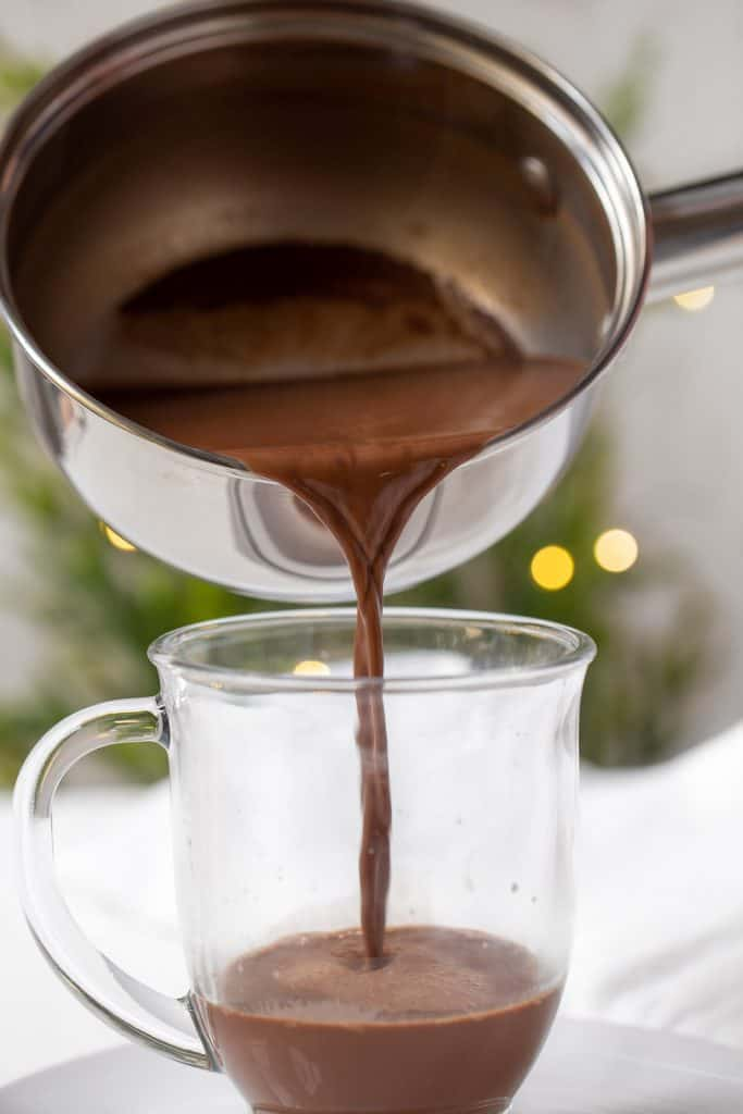 Hot chocolate being poured into a glass mug