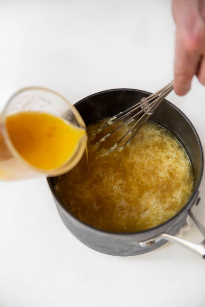 cup of egg yolks being whisk into hot broth