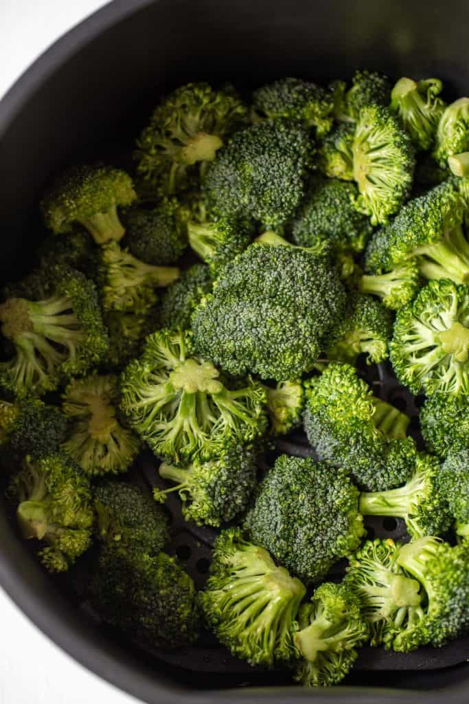 raw broccoli in air fryer basket