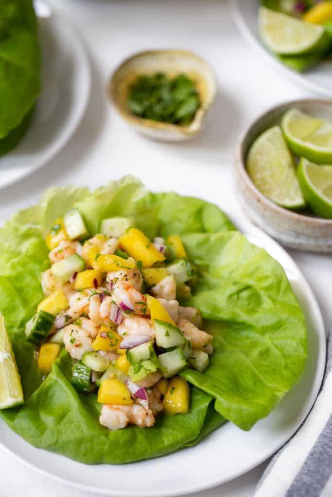 close up of lettuce wrap full of mango shrimp salsa