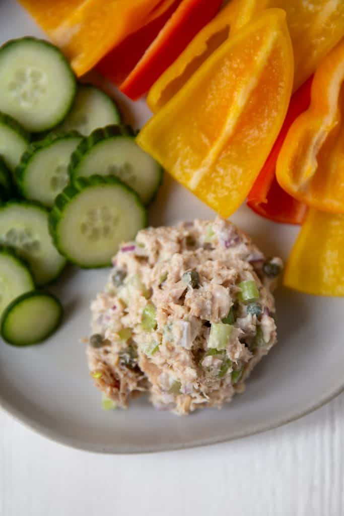 plate with tuna salad with sliced cucumbers and peppers