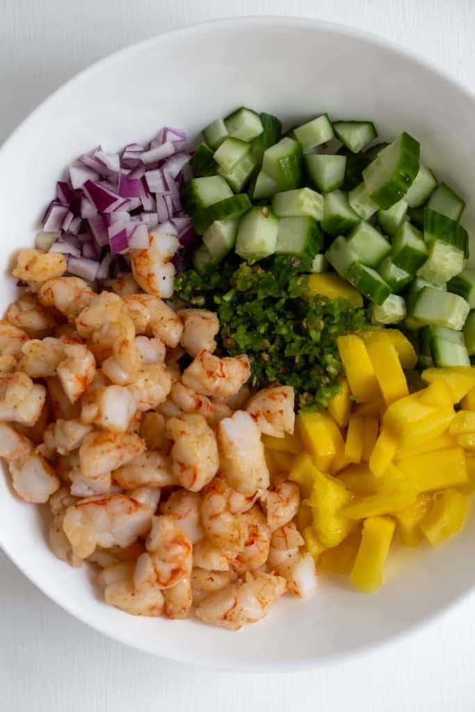 Bowl of ingredients to make mango shrimp salsa