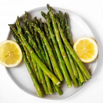 Cooked asparagus on a plate with fresh lemon.