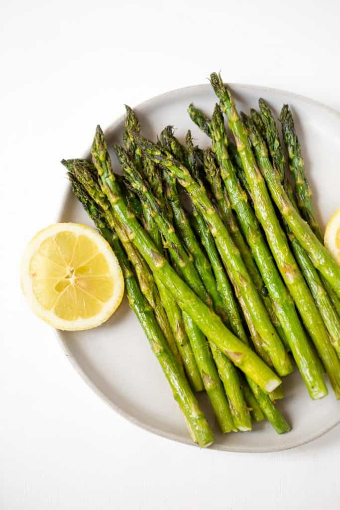 Close up of cooked asparagus on a plate with fresh lemon.