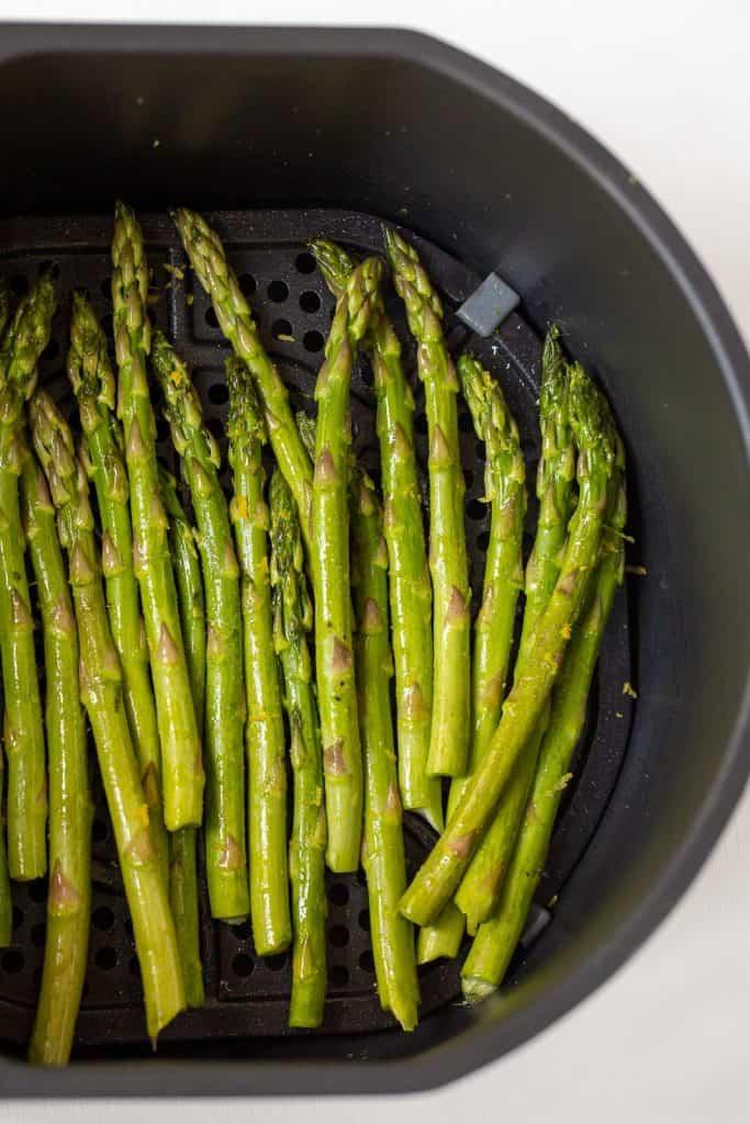 Seasoned asparagus in air fryer basket.