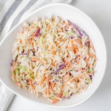 large bowl of green and purple cabbage combined with mayo.